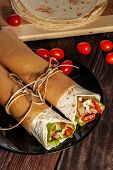 picture of sandwich wrap  - Mexican tortilla wrap with meat and vegetables on wood table - JPG