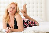 picture of lie  - Beautiful woman resting lying on a bed - JPG