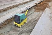 image of vibration plate  - Vibratory plate compactor compacting sand at road construction site - JPG
