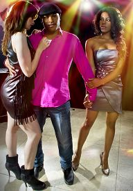 stock photo of swingers  - charming single man with two women at a nightclub - JPG