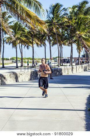 Man Jogs Along Along The Promenade At Ocean Drive In South Beach