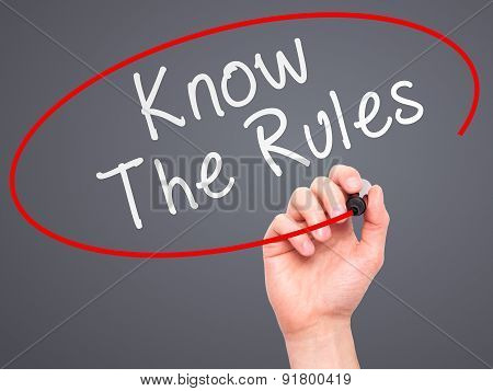Man Hand writing Know The Rules with marker on transparent wipe board.