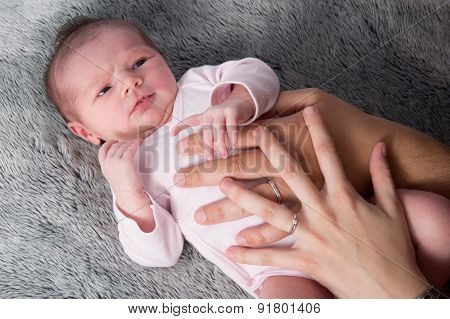 Close Up Of New Born Baby With Parents Hands On Belly