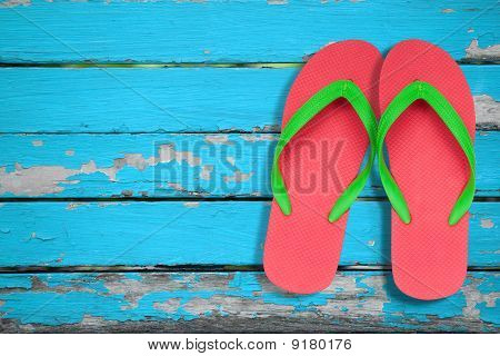 Red Ang Green Flip Flop Sandals On Blue Wood