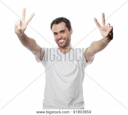 young casual man showing the victory gesture while smiling for the camera with a hand in his pocket. isolated on white background
