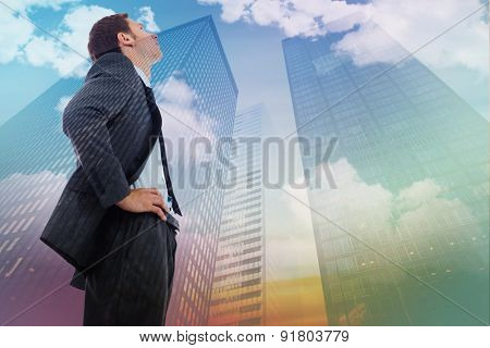 Stern businessman standing with hands on hips against low angle view of skyscrapers