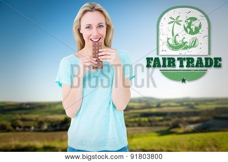 Smiling blonde eating bar of chocolate against scenic landscape