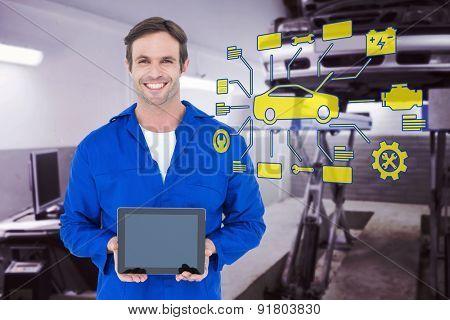 Happy mechanic holding digital tablet against auto repair shop