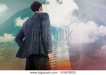 Businessman standing with hand on hip against low angle view of skyscrapers at sunset
