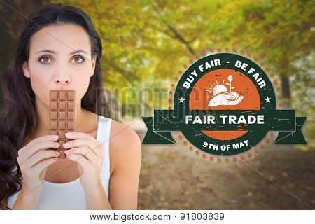 Pretty brunette eating bar of chocolate against country road along trees in the lush forest