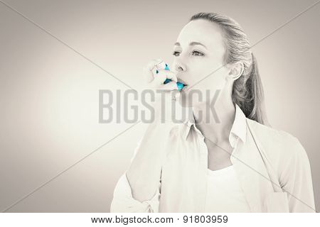 Pretty blonde using an asthma inhaler against grey vignette