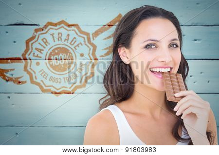 Pretty brunette eating bar of chocolate against painted blue wooden planks