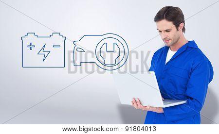 Mechanic using laptop over white background against grey vignette