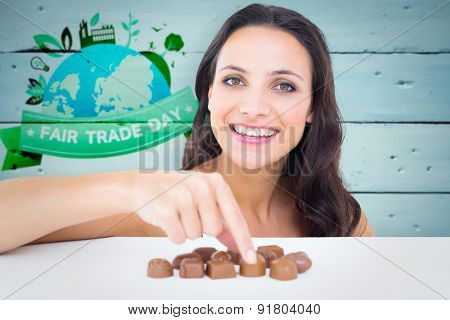 Pretty brunette picking out chocolate against painted blue wooden planks