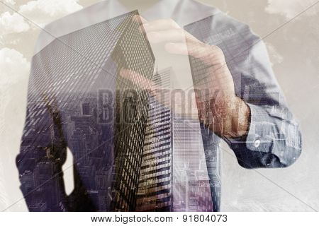 Hand of businessman showing smartphone against low angle view of skyscrapers