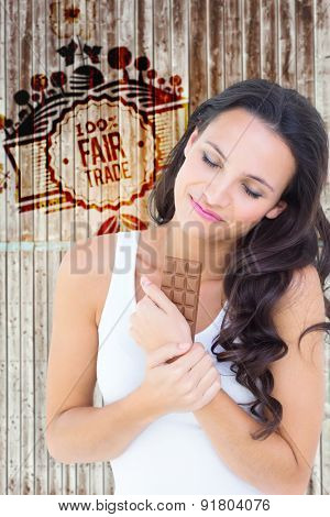 Pretty brunette eating bar of chocolate against wooden planks