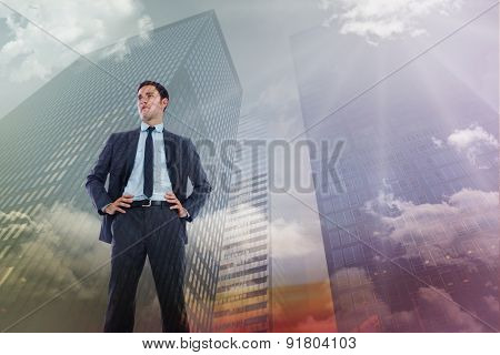 Serious businessman with hands on hips against low angle view of skyscrapers at sunset