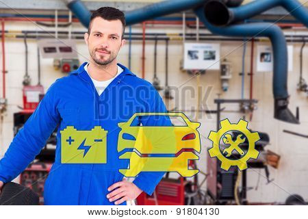 Smiling male mechanic holding tire against workshop