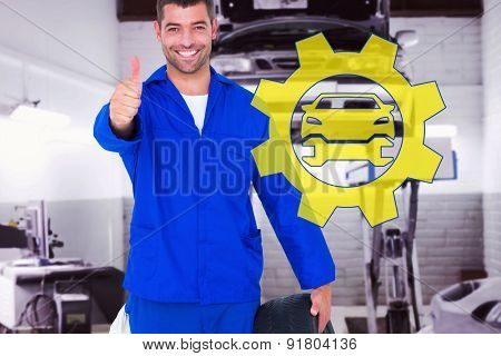 Mechanic with tire gesturing thumbs up against auto repair shop