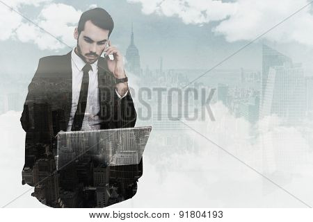 Businessman using laptop while phoning against new york