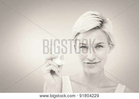 Pretty woman holding inhaler smiling at camera against grey vignette