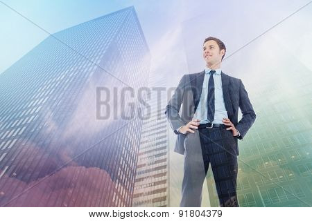 Happy businessman with hands on hips against low angle view of skyscrapers