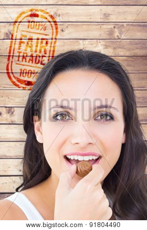 Pretty brunette eating chocolate candy against wooden planks