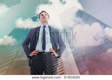 Happy businessman with hands on hips against skyscraper