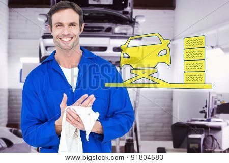 Confident mechanic wiping hand with napkin against auto repair shop