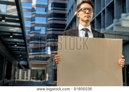 Businessman in a city street holding a blank banner