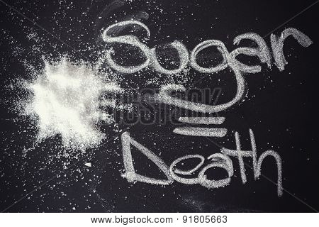 Sugar on black chalkboard from above.