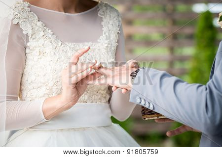 picture of woman putting wedding ring on man's hand