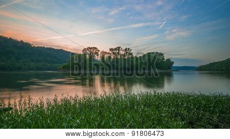 Island in a River with Pink and Blue Sunset Skies. River Grass. Distant Dam.