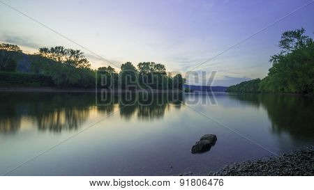 River Landscape After Sunset During Blue Hour. Reflective Water and Rocks.