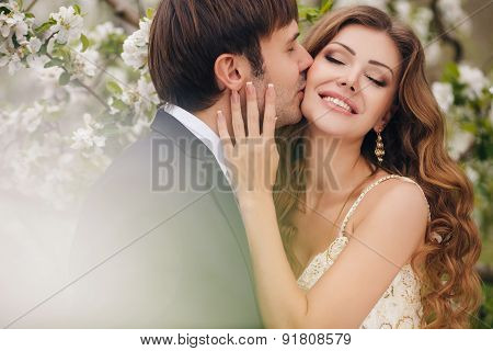 The groom kisses the bride in the flowered Park in the spring.