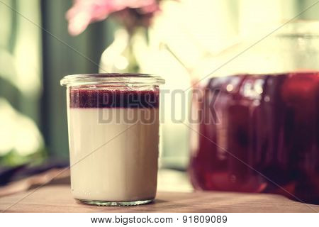 Traditional Italian dessert panna cotta with raspberries and red fruit tea.Wooden background.
