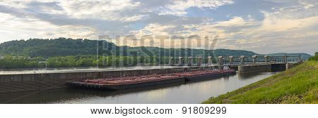 Lock and Dam on a River with an Oil Barge. Sky with Clouds.