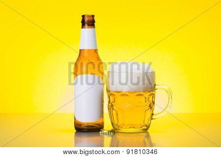 Mug With Foamy Beer And Empty Bottle