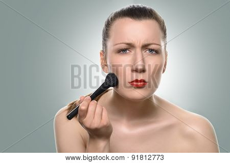 Young Woman Applying Blush On Her Cheeks