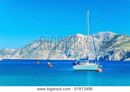 White yacht moored in sea bay of Greek Island