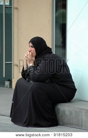 Young muslim woman sitting in front of the shop