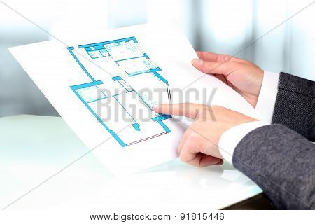 Real-estate Agent Showing House Plans To A Businessman.