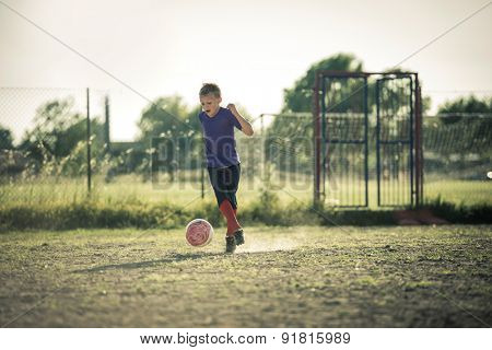 Excited young boy playing soccer