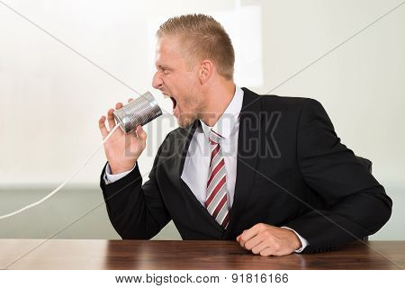 Businessman Screaming In Tin Cans Phone