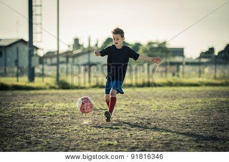 Young boy kicking ball