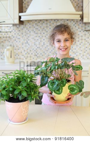 Smiling girl with houseplants in the kitchen