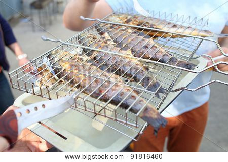 Closeup of four baked fish on the grill and tray
