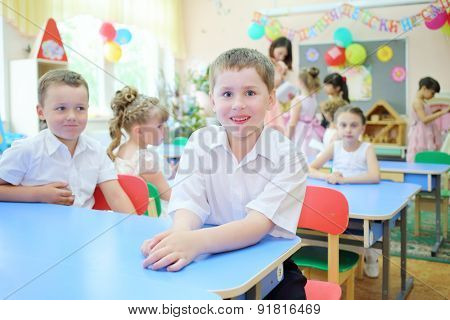 Portrait of a smiling boy in a group with seven children and educator in kindergarten