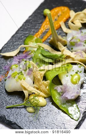 Marinated scallops served on a black slate.