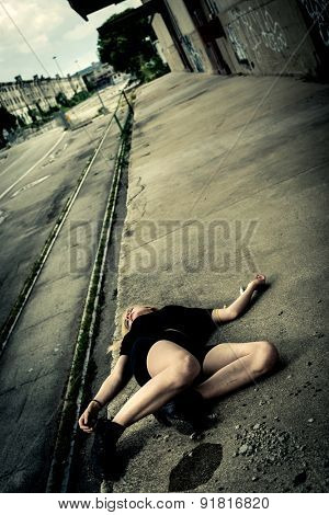 Yuong woman lying on the floor, maybe victim of violence or drug